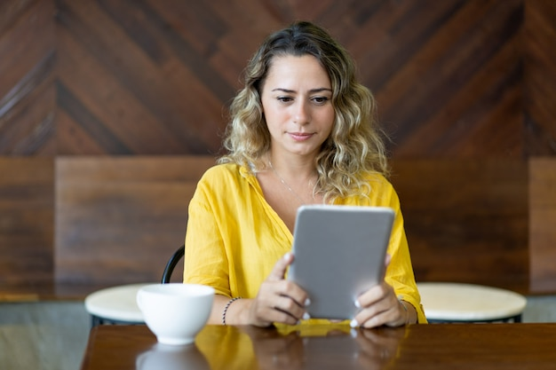 Pretty young woman concentrated on reading book on tablet