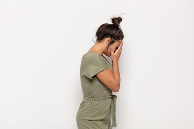 Довольно молодая женщина закрыла глаза руками с грустным, разочарованным взглядом отчаяния, плачет, вид сбоку