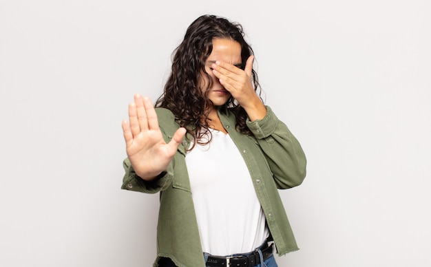 Pretty young woman covering face with hand and putting other hand up front to stop front, refusing photos