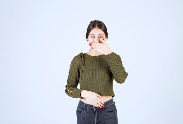 白い壁に彼女の口を覆っているかなり若い女性