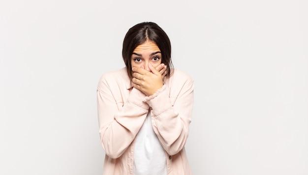 Довольно молодая женщина закрывает рот руками с шокированным, удивленным выражением лица, хранит секрет или говорит: ой