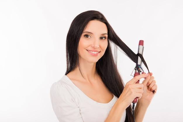 彼女の長い髪をカールするかなり若い女性