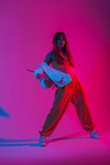 밝은 분홍색 네온 불빛이 있는 스튜디오에서 힙합 댄스를 추는 세련된 운동화를 신고 청소년 패션 운동복을 입은 예쁜 젊은 여성 댄서. 멋진 소녀는 스튜디오에서 다양한 색상의 춤을 즐깁니다.