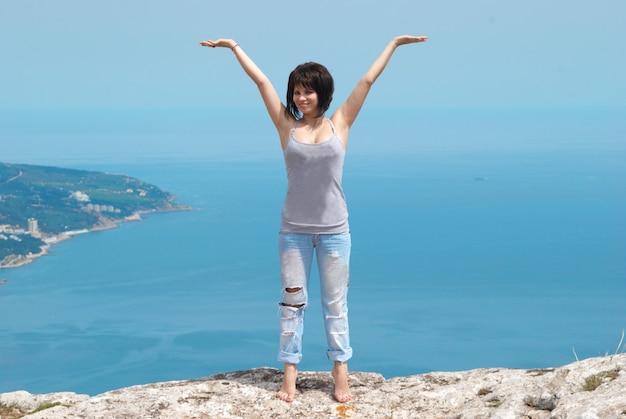 Довольно молодая женщина, танцующая на скале
