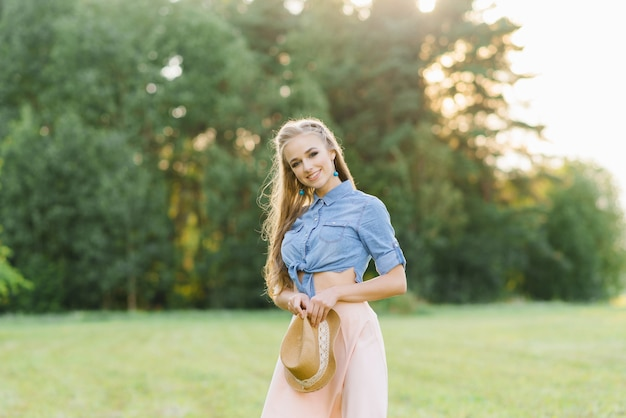A pretty young woman in a denim shirt and pink skirt holds a hat in her hands, she smiles and walks in nature in the summer