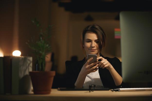 Довольно молодая женщина дизайнер, сидя в помещении в чате по телефону