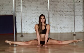 Pretty young woman does leg split sitting on the floor