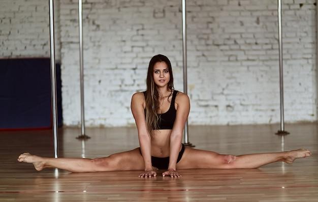 Довольно молодая женщина делает разделение ноги, сидя на полу