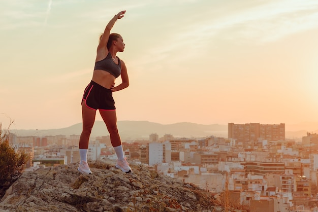 Pretty young woman does yoga overlooking the city at sunset outdoors