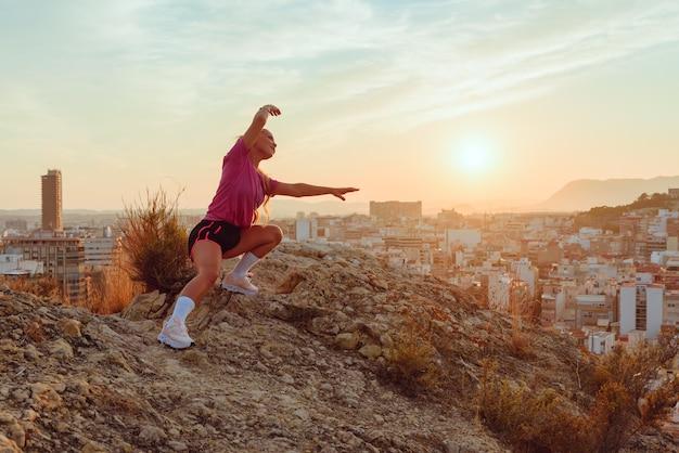 かなり若い女性が屋外の日没で街を見下ろすヨガをします