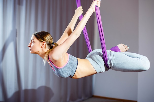 Pretty young woman doing antigravity yoga exercises