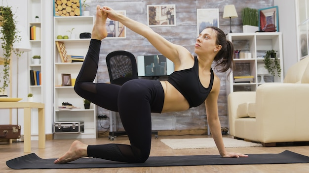 居間でバランスヨガの練習をしているかなり若い女性。健康的な生活様式。