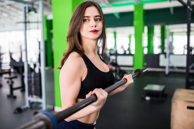 Pretty young woman doing exercises with barbell dressed up in fashion sportswear in sportclub