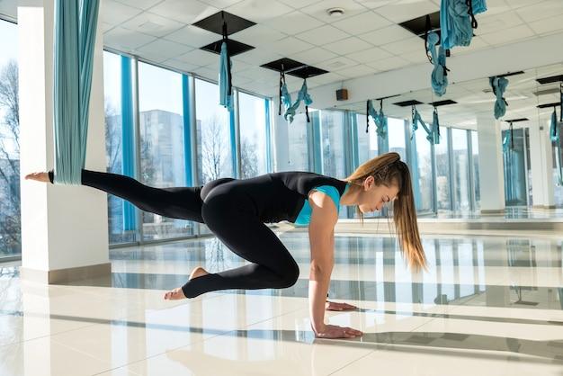 Довольно молодая женщина делает упражнения на растяжку йоги мухи в тренажерном зале фитнеса. здоровье, концепция йоги летать.