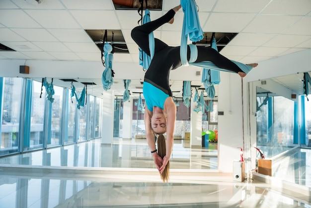 피트 니스 훈련 체육관에서 운동을 스트레칭 플라이 요가 하 고 꽤 젊은 여자. 건강, 비행 요가 개념.