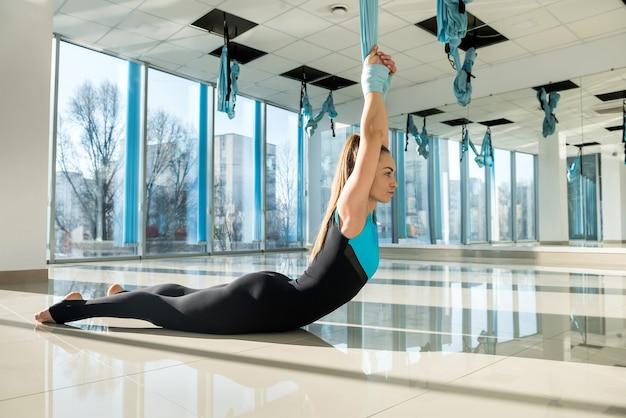 Довольно молодая женщина делает упражнения на растяжку йоги