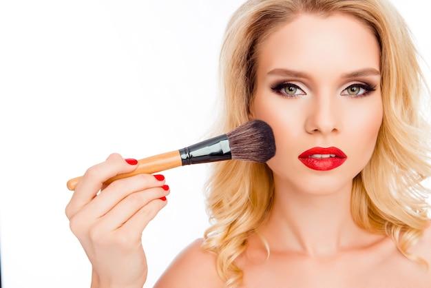Довольно молодая женщина делает макияж с порошковой кистью