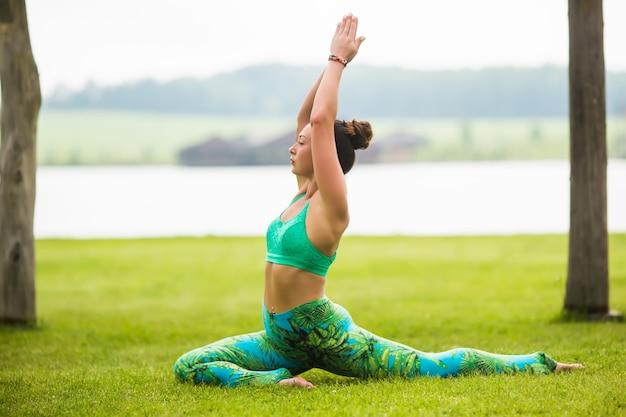 Довольно молодая женщина делает упражнения йоги в парке
