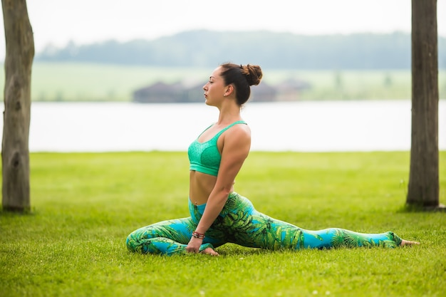 Pretty young woman doing yoga exercises in the park