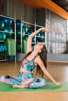 Pretty young woman doing yoga with eyes closed