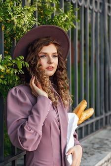バゲットを手にフランス風の服を着たかなり若い女性。フランスの女性スタイルのパリ。焼きたてのパンのバゲットを持って笑顔でスタイリッシュな服のクローズアップ。サイトまたはバナー用のコピースペース