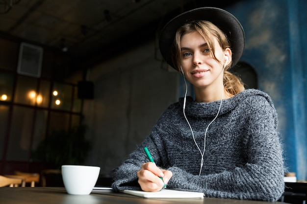 Pretty young woman dressed in sweater and hat sitting at the cafe table indoors, listening to music with earphones, drinking coffee, taking notes