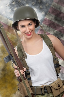 Pretty young woman dressed in wwii military uniform with helmet and rifle