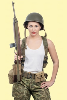 Pretty young woman dressed in wwii military uniform with helmet