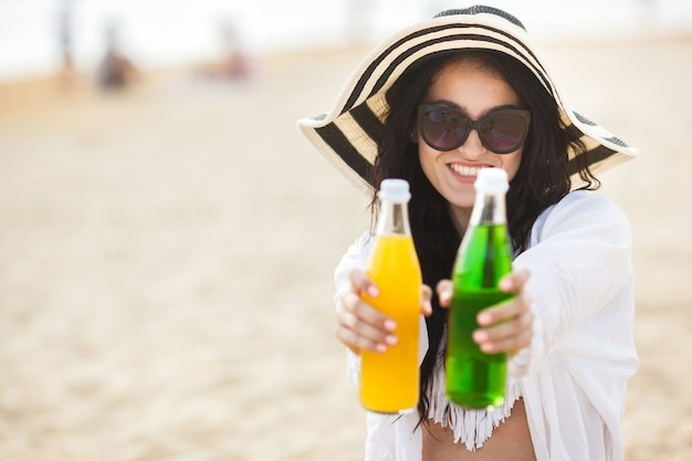 Pretty young woman drinking cocktail on the beach. attractive girl offering a drink. beautiful woman drinking lemonade