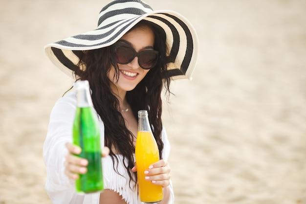 ビーチでカクテルを飲んでかなり若い女性。ドリンクを提供している魅力的な女の子。レモネードを飲む美しい女性
