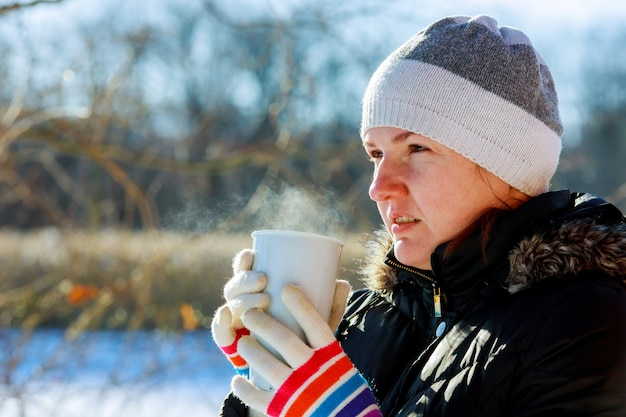 Pretty young woman drinking hot tea on a cold winter day