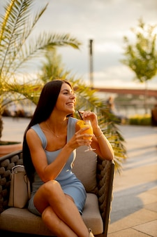 Довольно молодая женщина пьет апельсиновый сок в уличном кафе