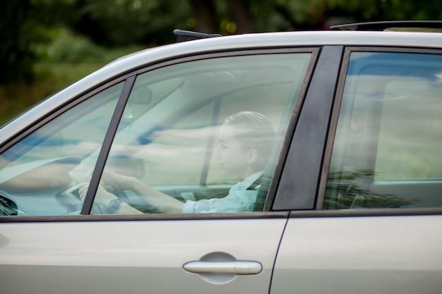 Красивая, молодая женщина за рулем автомобиля - приглашение в путешествие. прокат автомобилей или отпуск