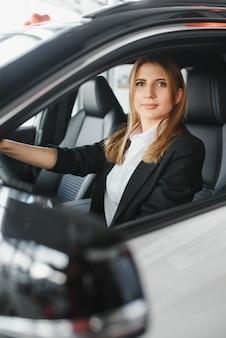 Довольно молодая женщина за рулем своей новой машины (цветное изображение; неглубокая глубина резкости)