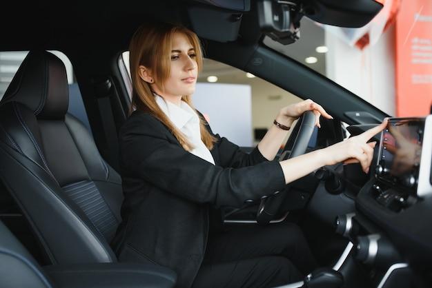 Довольно молодая женщина за рулем своей новой машины (цветное изображение; неглубокая глубина резкости) Premium Фотографии