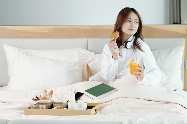 朝起きた後、良い本を持ってベッドに座ってクロワッサンを食べ、オレンジジュースを飲むかなり若い女性