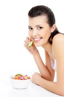 Donna abbastanza giovane che mangia insalata sana - isolata su bianco