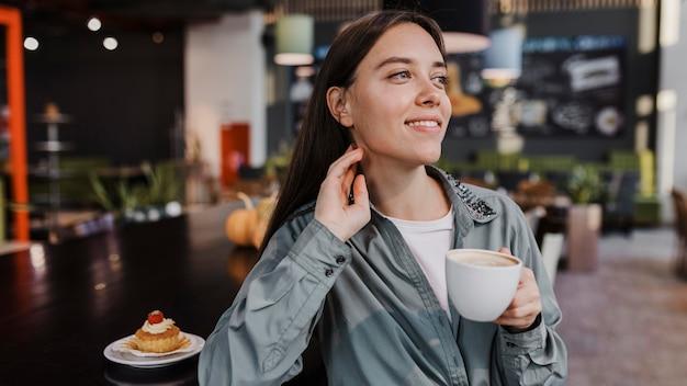 Довольно молодая женщина, наслаждаясь кофе-брейком