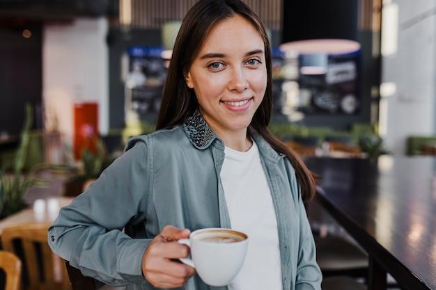 コーヒーカップを楽しんでいるかなり若い女性