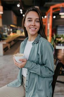 Довольно молодая женщина, наслаждаясь чашкой кофе