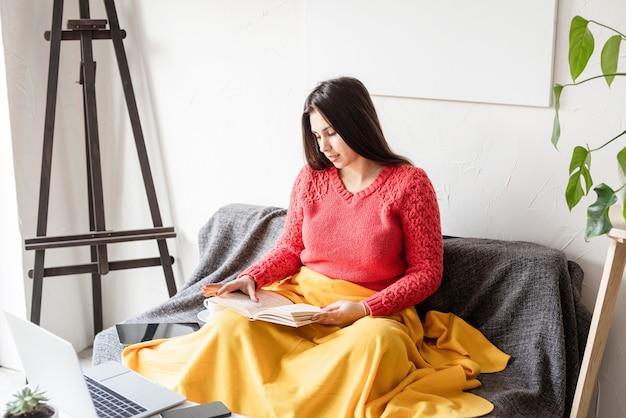 カジュアルな服と格子縞の喜びで笑ってソファに座って自宅で本を読んで楽しんでいるかなり若い女性
