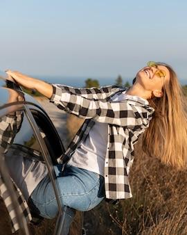Pretty young woman enjoying road trip