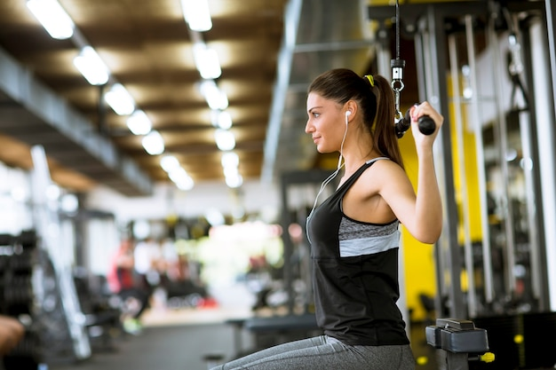 Pretty young woman exercises on an exercise machine at the gym listening to music