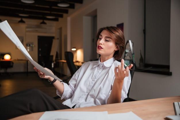 テーブルの上に足で座って、オフィスでスケッチを見ているかなり若い女性のファッションデザイナー