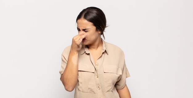 Pretty young woman feeling disgusted, holding nose to avoid smelling a foul and unpleasant stench