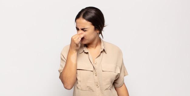 嫌悪感と不快な悪臭を嗅ぐのを避けるために鼻を持っているかなり若い女性