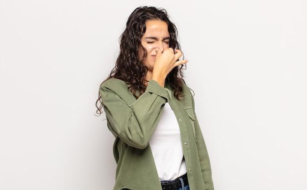 嫌悪感と不快な悪臭を嗅ぐのを避けるために鼻を保持しているかなり若い女性