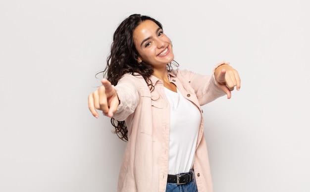 Довольно молодая женщина чувствует себя счастливой и уверенной, указывая на камеру обеими руками и смеясь, выбирая вас