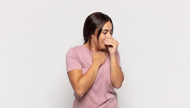 Довольно молодая женщина чувствует себя плохо с симптомами гриппа и болью в горле, кашляет с прикрытым ртом