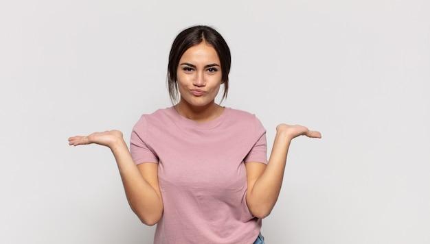 Довольно молодая женщина чувствует себя озадаченной и смущенной, сомневаясь, взвешивая или выбирая разные варианты с забавным выражением лица
